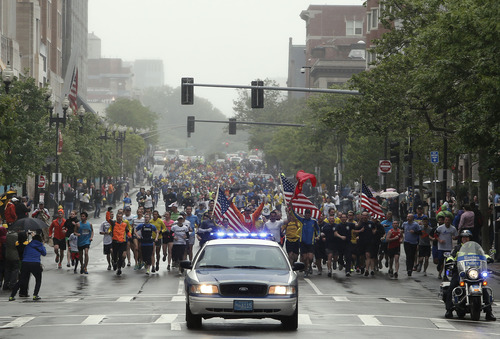 Runners who were unable to finish the Boston Marathon on April 15 because of the bombings head toward the finish line on Boylston Street after the city allowed them to finish the last mile of the race in Boston, Saturday, May 25, 2013. (AP Photo/Winslow Townson)