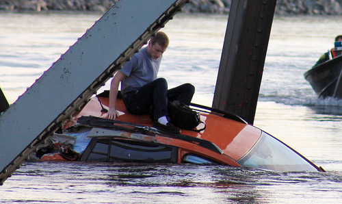 ADDS IDENTIFICATION OF MAN - In this photo provided by Francisco Rodriguez, Bryce Kenning sits atop his car that fell into the Skagit River after the collapse of the Interstate 5 bridge there minutes earlier Thursday, May 23, 2013, in Mount Vernon, Wash. (AP Photo/Francisco Rodriguez)