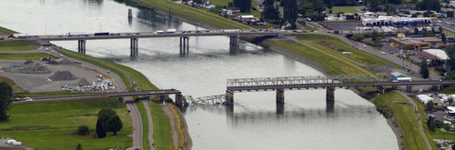 A collapsed section of the Interstate 5 bridge over the Skagit River is seen in an aerial view Friday, May 24, 2013, in Mt. Vernon, Wash. Part of the bridge collapsed Thursday evening, sending cars and people into the water when a an oversized truck hit the span, the Washington State Patrol chief said.  Washington Gov. Jay Inslee on Friday declared a state of emergency in three counties around the bridge, saying that the bridge collapse has caused extensive disruption, impacting the citizens and economy in Skagit, Snohomish and Whatcom Counties. (AP Photo/The Seattle Times, Mike Siegel)  MAGS OUT; NO SALES; SEATTLEPI.COM OUT; MANDATORY CREDIT