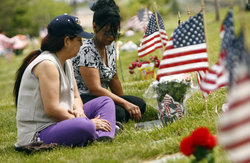 Bluffdale, UT--5/28/07--3:12:10 PM-- Juanita Rodriguez, left and sister Sonia Orozco visit the grave of their father Susano Torres Rodriguez at the Utah Veteran's Memorial Cemetery. Rodriguez served with the Tec 5 unit the Army during WWII.  ******** Veteran's Day ceremony featuring the 23rd Army Band Brass Quintet, a wreath ceremony, and remarks from House Speaker Greg Curtis and Ed Betenson.   Chris Detrick/Salt Lake Tribune File #_1CD5806    `