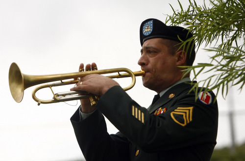 Bluffdale, UT--5/28/07--2:58:02 PM-- Staff Sgt. Dwight Bird, of the  23rd Army band-Utah National Guard, plays 'taps' at the end of the Memorial Day ceremony at the Utah Veteran's Memorial Cemetery.  ******** Memorial Day ceremony featuring the 23rd Army Band Brass Quintet, a wreath ceremony, and remarks from House Speaker Greg Curtis and Ed Betenson.   Chris Detrick/Salt Lake Tribune File #_1CD5784    `