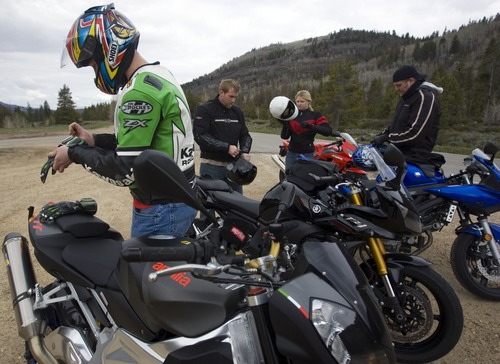 Motorcycle riders prepare to ride after brief break on the Mirror Lake Byway. The foursome, from left, Nick Visokey, Shane Stubbs, Virginia Clark and Spencer Ellis, all from Salt Lake City, said the ride was cold in the mountains on a mild Sunday afternoon in the Wasatch National Forest in the Uinta mountains May 25, 2008. Cooler than usual temperatures were present for the Memorial Day weekend and the snow persisted in the higher elevations closing roads and campgrounds. 05/25/2008 Jim Urquhart/The Salt Lake Tribune