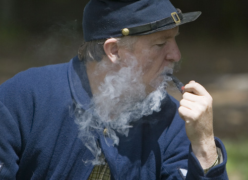 Jim Urquhart  |  The Salt Lake Tribune Playing the part of a Union Army soldier Steven Powell of Park City smokes a pipe in camp Saturday, May 29 2010 at a Civil War encampment in Fairfield.  Camp Floyd State Park in conjunction with the Utah Territorial Civilian Commission and Utah Civil War Association are hosting a Civil War Encampment Memorial Day Weekend at Camp Floyd State Park. The event allows visitors to experience camp life and participate in several activities performed by soldiers of the Civil War. Events include reenactments, encampments, storytelling, stagecoach rides, firearm and cannon demonstrations, marches, drills, 1861 period games, and photos in period uniform. 5/29/10