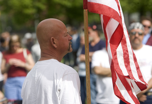 Al Hartmann  |  The Salt Lake Tribune   5/31/10 James Doty, a veteran of the army and navy from 1978-2003 holds a flag at a Memorial Day service in Pioneer Park where many homeless gathered Monday for a day long picnic sponsored by the Salt Lake Rescue Mission.
