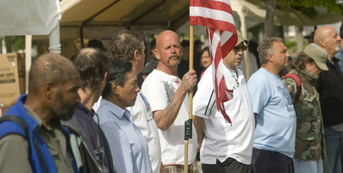 Al Hartmann  |  The Salt Lake Tribune   5/31/10 Al Hartmann  |  The Salt Lake Tribune   5/31/10 James Doty, a veteran of the army and navy from 1978-2003 holds a flag with other veterans of Salt Lake's streets at a Memorial Day service in Pioneer Park where many homeless gathered Monday for a day long picnic sponsored by the Salt Lake Rescue Mission.