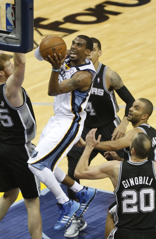 Memphis Grizzlies Mike Conley drives to the basket as San Antonio Spurs guard Manu Ginobili (20) and forward Matt Bonner (15) defend during the first half in Game 3 of the Western Conference finals NBA basketball playoff series in Memphis, Tenn., Saturday, May 25, 2013.  (AP Photo/Rogelio V. Solis)