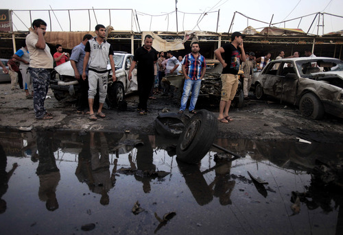 Iraqis gather at the scene of a car bomb attack at a used cars dealers parking lot in Habibiya neighborhood of eastern Baghdad, Iraq, Monday, May 27, 2013. A wave of car bombings tore through mostly Shiite Muslim neighborhoods of the Baghdad area, killing and wounding dozens of people, police said, in the latest outburst of an unusually intense wave of bloodshed roiling Iraq. The blasts are the latest indication that Iraq's security is rapidly deteriorating. (AP Photo/Karim Kadim)