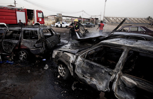 Iraqi firefighters distinguish a fire at the scene of a car bomb attack at a used cars dealers parking lot in Habibiya neighborhood of eastern Baghdad, Iraq, Monday, May 27, 2013. A wave of car bombings tore through mostly Shiite Muslim neighborhoods of the Baghdad area, killing and wounding dozens of people, police said, in the latest outburst of an unusually intense wave of bloodshed roiling Iraq. The blasts are the latest indication that Iraq's security is rapidly deteriorating. (AP Photo/ Karim Kadim)