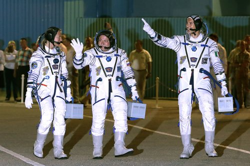 U.S. astronaut Karen Nyberg, left, Russian cosmonaut Fyodor Yurchikhin, center, and European Space Agency astronaut Luca Parmitano crew members of the mission to the International Space Station, ISS, gesture as walk prior the launch of their Soyuz-FG rocket at the Russian leased Baikonur cosmodrome, Kazakhstan, Tuesday, May 28, 2013. (AP Photo/Mikhail Metzel)