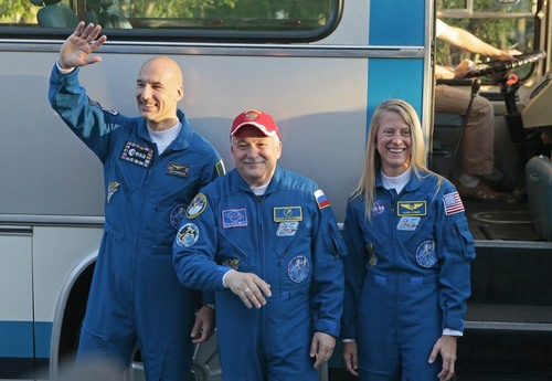 U.S. astronaut Karen Nyberg, right, Russian cosmonaut Fyodor Yurchikhin, center, and European Space Agency astronaut Luca Parmitano crew members of the mission to the International Space Station, ISS, gesture as stand at a bus prior leaving to the launch of their Soyuz-FG rocket at the Russian leased Baikonur cosmodrome, Kazakhstan, Tuesday, May 28, 2013. (AP Photo/Mikhail Metzel)
