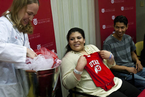 Chris Detrick  |  The Salt Lake Tribune Tracy Manuck, M.D., Maternal Fetal Medicine, gives Guillermina and Fernando Garcia a  Utes onesie during a press conference at the University of Utah Hospital Tuesday May 28, 2013. The couple welcomed quintuplets to the world on Sunday, the first set born in Utah in at least five years.