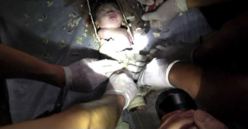 In this still image taken from video from Saturday May 25, 2013, rescue workers cut away the section of a sewage pipe where a newborn baby was trapped in Pujiang in east China's Zhejiang province. Chinese firefighters have rescued a newborn boy from a sewer pipe below a squat toilet, sawing out an L-shaped section and then delicately dismantling it to free the trapped baby, who greeted the rescuers with cries. A tenant heard the baby's sounds in the public restroom of a residential building in Zhejiang province in eastern China on Saturday and notified authorities, according to the state-run news site Zhejiang News. A video of the two-hour rescue that followed was broadcast widely on Chinese news programs and websites late Monday and Tuesday. (AP Photo)