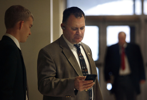 Scott Sommerdorf   |  The Salt Lake Tribune Clark Aposhian, center, checks his phone messages while waiting for a meeting in the House building at the Utah State Capitol complex, Wednesday, February 6, 2013. Aposhian spends long days at the capitol every day during the legislative session advocating for gun rights.  At left is Rep. Curt Oda's intern, Nate Osborne.