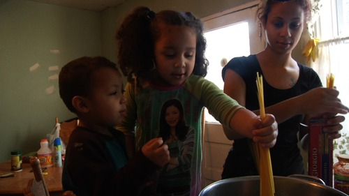 """Courtesy photo Barbie Izquierdo, right, an unemployed Philadelphia mom, cooks dinner with her children in a scene from the documentary """"A Place at the Table."""" The film discusses the problem of hunger in America."""