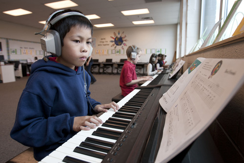 Steve Griffin | The Salt Lake Tribune Whittier Elementary School third grader, Aizhy Lumacad, plays the piano during class at the Salt Lake City school. The school is losing its federal Title I  funding next year, and a school-wide music program is threatened  by the loss. It gives every Whittier student a chance to learn music with an emphasis on the piano.