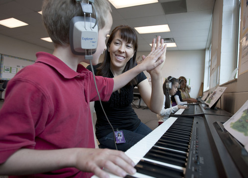 Steve Griffin | The Salt Lake Tribune Whittier Elementary School third grader, Zach Tragakis, high-fives his music teacher, Colette Lofgren, during piano class at the Salt Lake City school. The school is losing its federal Title I funding next year, and a school-wide music program is threatened by the loss. It gives every Whittier student a chance to learn music with an emphasis on the piano.