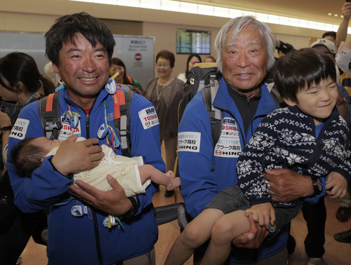 Eighty-year-old Japanese climber Yuichiro Miura, right, who became the oldest conqueror of Mount Everest on last Thursday, and his son Gota, left, are welcomed by his grandson Yugo, 5, right, and granddaughter Megumi upon their arrival at Haneda International Airport in Tokyo, Wednesday, May 29, 2013. Miura, a Japanese former extreme skier, conquered the mountain on May 23 despite undergoing heart surgery in January for an irregular heartbeat, or arrhythmia, his fourth heart operation since 2007. He also broke his pelvis and left thigh bone in a 2009 skiing accident. (AP Photo/Itsuo Inouye)