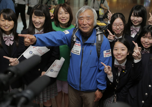Eighty-year-old Japanese climber Yuichiro Miura, fourth left, who became the oldest conqueror of Mount Everest on last Thursday, poses for photographers with his daughter Emiri, third left, and his CLARK Memorial International High School students upon his arrival at Haneda International Airport in Tokyo, Wednesday, May 29, 2013. Miura, a Japanese former extreme skier, conquered the mountain on May 23 despite undergoing heart surgery in January for an irregular heartbeat, or arrhythmia, his fourth heart operation since 2007. He also broke his pelvis and left thigh bone in a 2009 skiing accident. (AP Photo/Itsuo Inouye)