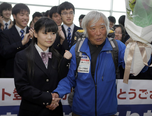 Eighty-year-old Japanese climber Yuichiro Miura, right, who became the oldest conqueror of Mount Everest on last Thursday, is welcomed by his CLARK Memorial International High School students upon his arrival at Haneda International Airport in Tokyo, Wednesday, May 29, 2013. Miura, a Japanese former extreme skier, conquered the mountain on May 23 despite undergoing heart surgery in January for an irregular heartbeat, or arrhythmia, his fourth heart operation since 2007. He also broke his pelvis and left thigh bone in a 2009 skiing accident. (AP Photo/Itsuo Inouye)