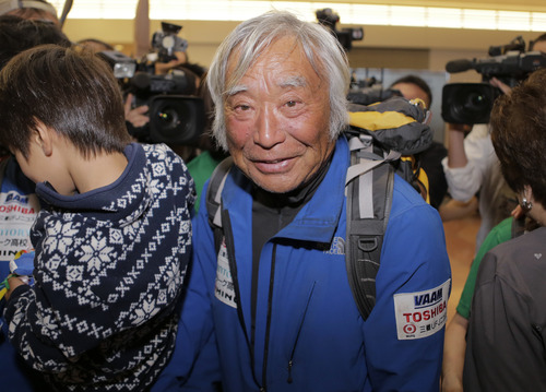 Eighty-year-old Japanese climber Yuichiro Miura, who became the oldest conqueror of Mount Everest on last Thursday, smiles upon his arrival at Haneda International Airport in Tokyo, Wednesday, May 29, 2013. Miura, a Japanese former extreme skier, conquered the mountain on May 23 despite undergoing heart surgery in January for an irregular heartbeat, or arrhythmia, his fourth heart operation since 2007. He also broke his pelvis and left thigh bone in a 2009 skiing accident. (AP Photo/Itsuo Inouye)
