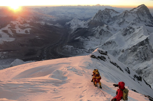 In this image released by mountain guide Adrian Ballinger of Alpenglow Expeditions and taken at sunrise on Saturday, May 18, 2013, climbers make their way to the summit of Mount Everest, in the Khumbu region of the Nepal Himalayas.  Nepal celebrated the 60th anniversary of the conquest of Mount Everest on Wednesday, May 29, 2013, by honoring climbers who followed in the footsteps of Edmund Hillary and Tenzing Norgay.  (AP Photo/Alpenglow Expeditions, Adrian Ballinger) MANDATORY CREDIT, EDITORIAL USE ONLY