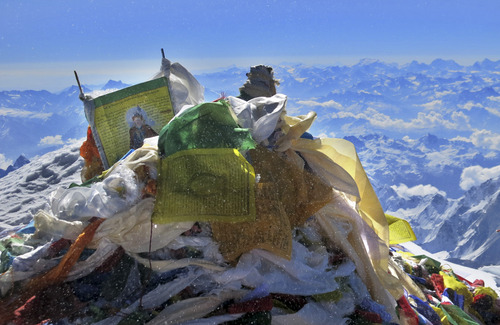 In this picture released by mountain guide Adrian Ballinger of Alpenglow Expeditions and taken Saturday, May 18, 2013, Tibetan Buddhist prayer flags are seen on the summit of Mount Everest, in the Khumbu region of the Nepal Himalayas.  Nepal celebrated the 60th anniversary of the conquest of Mount Everest on Wednesday, May 29, 2013, by honoring climbers who followed in the footsteps of Edmund Hillary and Tenzing Norgay.(AP Photo/Alpenglow Expeditions)