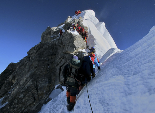 In this picture released by mountain guide Adrian Ballinger of Alpenglow Expeditions and taken Saturday, May 18, 2013, climbers navigate the Hillary Step just below the summit of Mount Everest, in the Khumbu region of the Nepal Himalayas. Nepal celebrated the 60th anniversary of the conquest of Mount Everest on Wednesday by honoring climbers who followed in the footsteps of Edmund Hillary and Tenzing Norgay. (AP Photo/Alpenglow Expeditions, Adrian Ballinger)