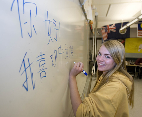 """Paul Fraughton     Salt Lake Tribune Skyline High School student, Kelsey Paulding, writes"""" I like my Chinese class"""" on the board. She will be traveling to China this summer after winning a fellowship."""