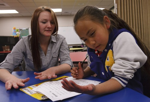 Leah Hogsten  |  The Salt Lake Tribune Makenna Hill helps Lyse Guerrero, 8, with her schoolwork at the Roy Boy's and Girls Club, Thursday, May 2, 2013.