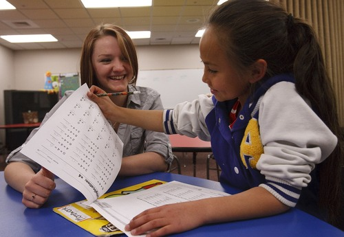 Leah Hogsten  |  The Salt Lake Tribune Makenna Hill helps Lyse Guerrero, 8, with her schoolwork at the Roy Boy's and Girls Club.