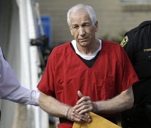 FILE - In this Oct. 9, 2012 file photo, former Penn State University assistant football coach Jerry Sandusky is taken from the Centre County Courthouse after being sentenced to at least 30 years in prison in the child sexual abuse scandal that brought shame to Penn State and led to coach Joe Paterno's downfall, in Bellefonte, Pa. The family of late coach Joe Paterno will be joined by former players and others connected to Penn State in a lawsuit that seeks to overturn the NCAA's strict sanctions against the football program for the Sandusky child sex abuse scandal. Paterno family lawyer Wick Sollers says the 40-page suit will be filed Thursday, May 30, 2013 in state court in Centre County, home of Penn State's main campus.  (AP Photo/Matt Rourke, File)