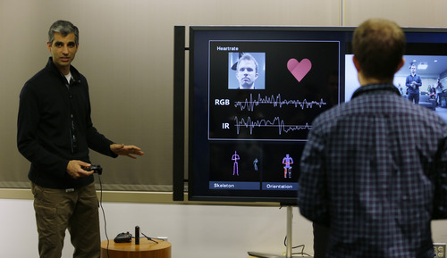 Kareem Choudhry, left, development manager for Microsoft's Kinect motion-sensing device for the Xbox, demonstrates how the new Kinect for the next-generation Xbox One entertainment and gaming console system reads facial features and other visual indications to approximate the heart rate of a user during a demonstration, Tuesday, May 21, 2013, in Redmond, Wash. (AP Photo/Ted S. Warren)