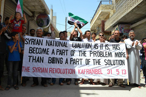 This citizen journalism image provided by Edlib News Network, ENN, which has been authenticated based on its contents and other AP reporting, show anti-Syrian regime protesters carrying a banner during a demonstration in Kafr Nabil town, in Idlib province, northern Syria, Friday May 31, 2013. Syrian troops on Friday attacked a convoy trying to evacuate the wounded from a central town near the border with Lebanon, killing many people, as rebel reinforcements infiltrated the besieged area to fight government forces backed by Lebanese Hezbollah fighters, activists said. (AP Photo/Edlib News Network ENN)