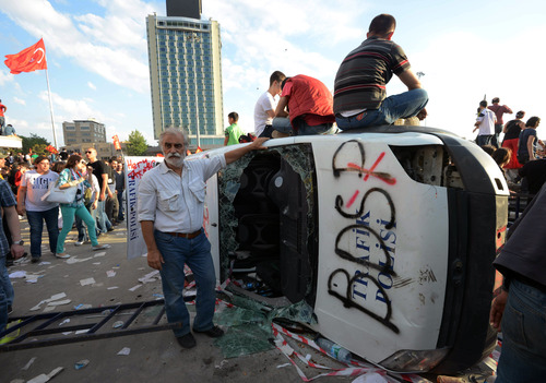 Turkish protesters seen with a destroyed car at the city's main Taksim Square in Istanbul, Turkey, Saturday, June 1, 2013. Turkish police retreated from a main Istanbul square Saturday, removing barricades and allowing in thousands of protesters in a move to calm tensions after furious anti-government protests turned the city center into a battlefield. A second day of national protests over a  violent police raid of an anti-development sit-in in Taksim square has revealed the depths of anger against Prime Minister Recep Tayyip Erdogan, who many Turks view as increasingly authoritarian and dismissive of opposing views.(AP Photo)