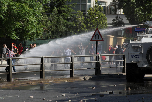 Turkish youths throw stones as they clash with security forces in Ankara, Turkey, Saturday, June 1, 2013. Turkish police retreated from a main Istanbul square Saturday, removing barricades and allowing in thousands of protesters in a move to calm tensions after furious anti-government protests turned the city center into a battlefield. A second day of national protests over a  violent police raid of an anti-development sit-in in Taksim square has revealed the depths of anger against Prime Minister Recep Tayyip Erdogan, who many Turks view as increasingly authoritarian and dismissive of opposing views.(AP Photo/Burhan Ozbilici)