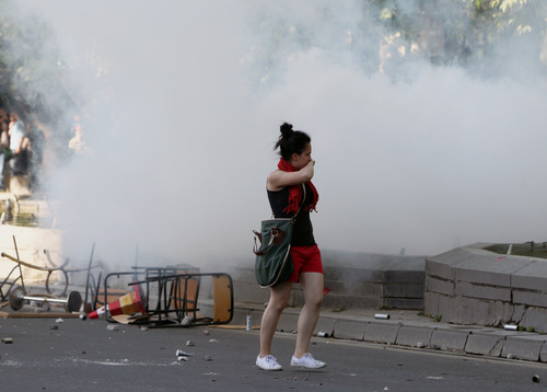A young woman runs as thousands of Turkish youths gathered at the city's main Kizilay Square and clashed with security forces in Ankara, Turkey, Saturday, June 1, 2013. Turkish police retreated from a main Istanbul square Saturday, removing barricades and allowing in thousands of protesters in a move to calm tensions after furious anti-government protests turned the city center into a battlefield. A second day of national protests over a  violent police raid of an anti-development sit-in in Taksim square has revealed the depths of anger against Prime Minister Recep Tayyip Erdogan, who many Turks view as increasingly authoritarian and dismissive of opposing views.(AP Photo/Burhan Ozbilici)