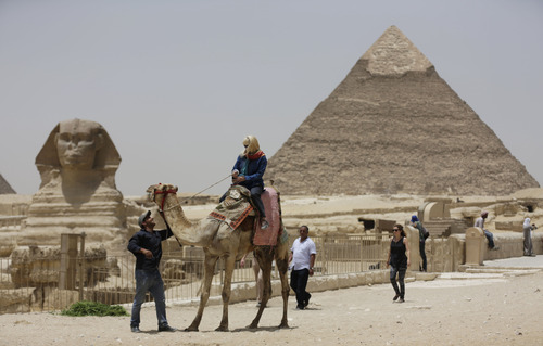 "In this photo taken Friday, May 31, 2013, a tourist takes a camel ride at the Giza Pyramids in Giza, Egypt. A statement by Egypt's Antiquities' Ministry Saturday, June 1, 2013 says a U.S. Embassy security warning sent to citizens to be extra cautious for their safety in the area of the Pyramids is baseless. Earlier in the week, the U.S. Embassy in Cairo sent a message to its citizens warning them to ""elevate their situational awareness when traveling to the Pyramids"" due to a ""lack of visible security or police"" in the area. (AP Photo/Hiro Komae)"