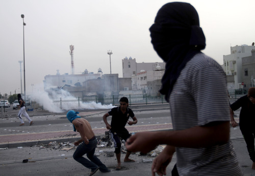 Bahraini anti-government protesters clash with riot police firing tear gas in Karzakan village, Bahrain, on Saturday, June, 1, 2013. Clashes broke out after a traditional procession marking third day after the death of Sayed Omran Sayed Hameed, 26, who died from excessive tear gas inhalation, according to family. (AP Photo/Hasan Jamali)