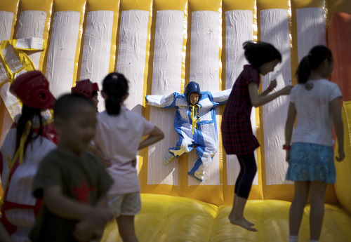 A child plays on a sticky wall as others jump on an inflatable balloon bouncer on International Children's Day organized by the Chinese Foreign Affairs Office at Children's Palace of Dongcheng district in Beijing Saturday, June 1, 2013. (AP Photo/Andy Wong)