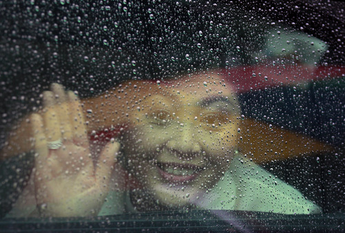 Thailand's Prime Minister Yingluck Shinawatra waves from a car window in a rain outside the Deepaduttamara Buddhist temple in Colombo, Sri Lanka, Saturday, June 1, 2013. Yingluck arrived in Sri Lanka Friday for a two-day official visit aimed at strengthening bilateral relations between the two countries. (AP Photo/Eranga Jayawardena)