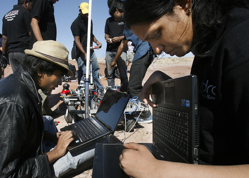 "Scott Sommerdorf  |  The Salt Lake Tribune The SRM University team from Chennai, India, including Jagadeesh RB, left, and Alekhya G, right, frantically work to repair their rover to get it ready for the South course at the University Rover Challenge outside Hanksville, Friday May 31, 2013. The rovers were required to navigate the course and distribute items to various ""astronauts"" along the course. Their rover was not able to get going."