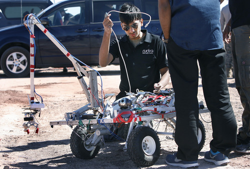 "Scott Sommerdorf  |  The Salt Lake Tribune Akshat Agrawal of the SRM University team from Chennai, India, yanks out a cord as he frantically works to repair their rover to get it ready for the South course at the University Rover Challenge outside Hanksville, Friday May 31, 2013. The rovers were required to navigate the course and distribute items to various ""astronauts"" along the course. Their rover was not able to get going."