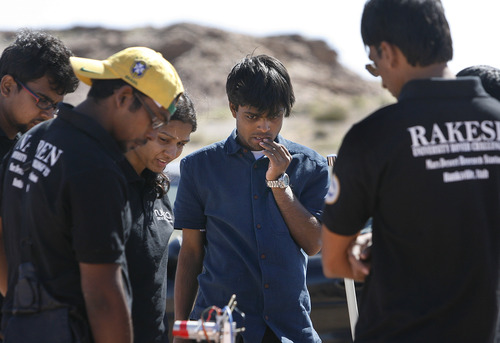 "Scott Sommerdorf   |  The Salt Lake Tribune Manoj Kumar Sharma, center, of the SRM University team from Chennai, India, ponders the problems their rover is experiencing as the team works to repair their rover to get it ready to take to the South course at the University Rover Challenge outside Hanksville, Friday May 31, 2013. The rovers were required to navigate the course and distribute items to various ""astronauts"" along the course. Their rover was not able to get going."