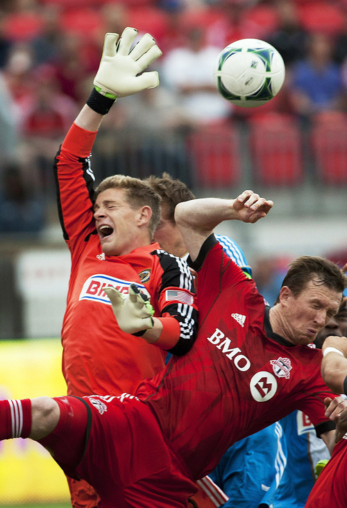 Toronto FC's Steven Caldwell, right, collides with Philadelphia Union goalie Chris Konopka during the first half of an MLS soccer game action Saturday June 1, 2013, in Toronto. (AP Photo/The Canadian Press, Aaron Vincent Elkaim)