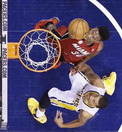 Miami Heat guard Norris Cole goes up for s shot against Indiana Pacers guard George Hill during the first half of Game 6 of the NBA Eastern Conference basketball finals in Indianapolis, Saturday, June 1, 2013. (AP Photo/Michael Conroy)