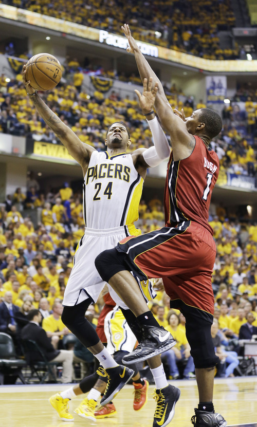 Indiana Pacers forward Paul George (24) goes up for a shot against Miami Heat center Chris Bosh (1) during the second half of Game 6 of the NBA Eastern Conference basketball finals in Indianapolis, Saturday, June 1, 2013. (AP Photo/Michael Conroy)