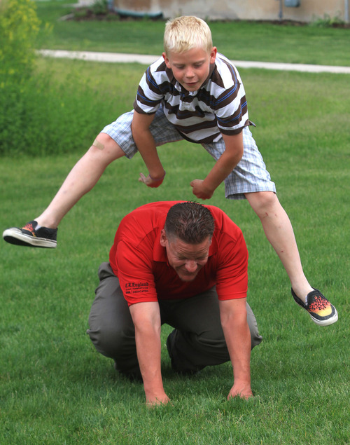 Rick Egan  |  The Salt Lake Tribune  Tristan King, 10, jumps over Darren King at they play leapfrog in a park near their home, one year after King's weight loss surgery. Wednesday, May 29, 2013.