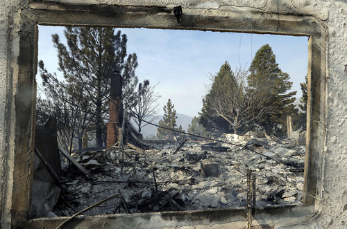 A window frames the view of one of at least five structures destroyed or severely damaged in Lake Hughes, Calif., early Sunday, June 2, 2013. Erratic wind fanned a blaze in the Angeles National Forest to nearly 41 square miles early Sunday, after fast-moving flames triggered the evacuation of nearly 1,000 homes in Lake Hughes and Lake Elizabeth, officials said. (AP Photo/Reed Saxon)