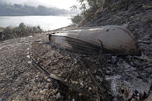 One boat lies melted on the shore of Lake Hughes in Lake Hughes, Calif., early Sunday, June 2, 2013. Erratic winds fanned a blaze in the Angeles National Forest to nearly 41 square miles early Sunday, after fast-moving flames triggered the evacuation of nearly 1,000 homes in Lake Hughes and Lake Elizabeth, officials said. (AP Photo/Reed Saxon)