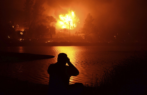 A local resident looks at his neighbors 2 story house fully involved in fire as one of several homes now destroyed as firefighters battling into a fourth day wildfire in the Angeles National Forest near the Lake Hughes areas early Sunday morning June 2,2013.  The Powerhouse Fire remained at 15 percent containment after ravaging over 5,600 acres of the forest by Saturday evening. Lake Hughes CA. June 2,2013. Photo by Gene Blevins/LA Daily News